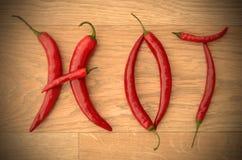 La pimienta de chiles roja de Pimienta pone letras a deletreo CALIENTE en la madera Imágenes de archivo libres de regalías