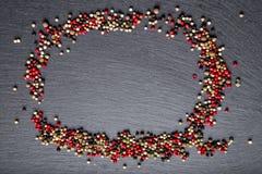 La pimienta dispersó en la pizarra, visión superior, un lugar para una inscripción Foto de archivo libre de regalías