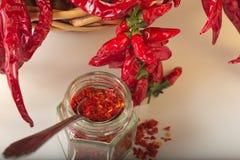 La pimienta roja picante molió en el tarro de cristal, con pimientas secadas sanas en la cesta Foto de archivo