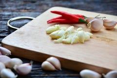 la pimienta y el ajo de chile de las especias pusieron a la tabla de cortar de madera en el wo foto de archivo libre de regalías