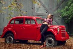 La pin-up in jeans ed in una camicia di plaid sta appoggiandosi una retro automobile rossa russa fotografia stock