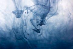 La pintura azul de la acuarela cae en agua con el fondo blanco Imagenes de archivo