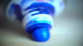 La pintura azul se exprime fuera del tubo blanco sobre una paleta de madera, tiroteo macro metrajes