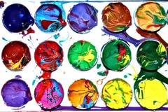 La pintura colorida de la acuarela manchó la caja de colores ocasional mezclados del bebé Foto de archivo