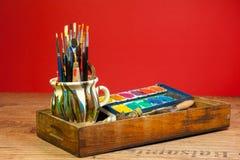 La pintura creativa de la actividad suministra colores de los cepillos en la apariencia vintage de madera de la caja Foto de archivo