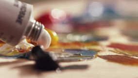 La pintura de aceite blanco se exprime fuera del tubo en superficie de la paleta de madera almacen de video