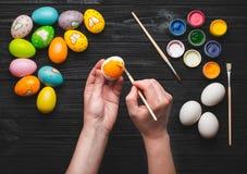La pintura de Hads eggs para el día de fiesta de Pascua en la tabla de madera Fotos de archivo