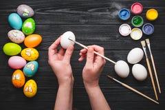 La pintura de Hads eggs para el día de fiesta de Pascua en la tabla de madera Imagenes de archivo