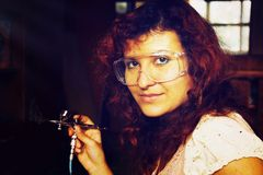 La pintura de la mujer joven con el equipo del aerógrafo y el aerógrafo disparan contra Imagenes de archivo