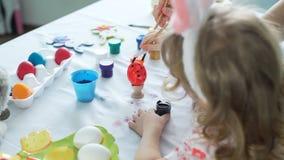 La pintura de la niña puntea en el huevo de Pascua metrajes