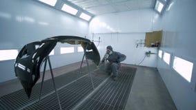 La pintura del coche, hombre profesional en traje protector pinta la pieza del automóvil en cámara brillantemente de pintura en e metrajes
