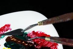 La pintura se mancha en una superficie blanca de la porcelana Están después dos espátulas artísticas Los movimientos de la pintur foto de archivo