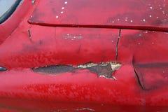 La pintura vieja del coche agrietó la grieta del color rojo con el insid oxidado de acero imagen de archivo libre de regalías