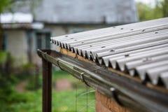 La pioggia cade dal tetto nel tubo di scarico Fotografie Stock Libere da Diritti