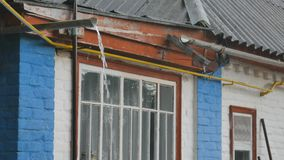 La pioggia che cade sulla vecchia casa riempie le grondaie della casa stock footage