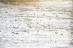 La pioggia scuoia giù alla via le gocce di pioggia sono visibili nella priorità alta c'è una pozza fangosa Fotografia Stock Libera da Diritti