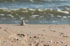 La pirámide se hace de las piedras blancas contra la perspectiva de ondas del mar fotos de archivo