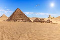 La piramide di Menkaure ed i tre compagni della piramide nel deserto di Giza immagini stock