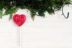 La piruleta del caramelo del corazón y la guirnalda de la Navidad se enciende con el sujetador verde Imagen de archivo