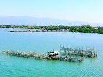 La pisciculture en mer, est après un bateau de pêche Montagne, mer, arbre, Image stock