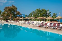 La piscina con los sunbeds y los paraguas está cerca del mar Concepto de turismo fotos de archivo libres de regalías