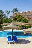 La piscina, parasoles de playa y el Mar Rojo en Egipto Foto de archivo