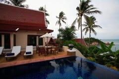 La piscina tailandesa de los chalets, ociosos del sol al lado del jardín adentro es bahía del océano Foto de archivo libre de regalías