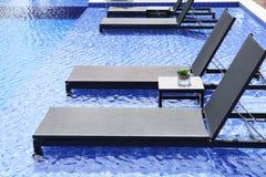 La piscina y las sillas acuestan con agua azul Foto de archivo libre de regalías