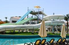 La piscine extérieure avec l'eau et les glissières d'eau chaudes claires bleues siffle des vacances dans un pays exotique chaud t photo libre de droits