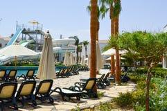 La piscine extérieure avec l'eau et les glissières d'eau chaudes claires bleues siffle des vacances dans un pays exotique chaud t photo stock