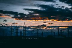 La pista de tierra del camino de las líneas eléctricas con el cielo dramático se nubla el fondo imágenes de archivo libres de regalías