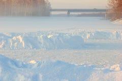 La pista di pattinaggio dei bambini, un ponte e un inverno annebbiano sopra il fiume congelato Fotografia Stock