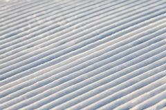 La pista diagonale di gatto delle nevi allinea su un fondo di struttura del pendio dello sci Immagine Stock Libera da Diritti