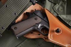 La pistola del potro en pistolera y la correa mienten en la chaqueta militar Imagen de archivo