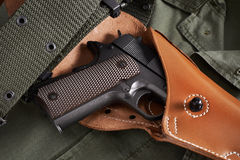 La pistola del puledro in custodia per armi e la cinghia si trovano sul rivestimento militare Immagine Stock
