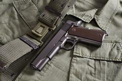 La pistola e la cinghia del puledro si trovano sul rivestimento militare Fotografia Stock