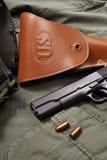 La pistola e la custodia per armi del puledro si trovano sul rivestimento militare Fotografie Stock