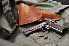 La pistola, la custodia per armi e la cinghia della pistola del puledro si trovano sul rivestimento militare Fotografia Stock
