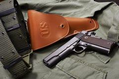 La pistola, la custodia per armi e la cinghia della pistola del puledro si trovano sul rivestimento militare Fotografie Stock