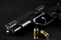 La pistola nera si trova su un fondo nero accanto alle pallottole immagine stock