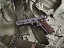 La pistola y la correa del arma del potro mienten en la chaqueta militar Fotos de archivo libres de regalías
