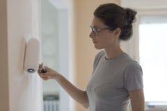 La pittura della donna mura a casa con un rullo di pittura fotografia stock