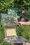 La pittura maschio dell'artista sull'aria del plein fiorisce le peonie rosa che dipingono sulla natura Fotografia Stock Libera da Diritti