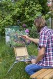 La pittura maschio dell'artista sull'aria del plein fiorisce le peonie rosa che dipingono sulla natura Immagine Stock Libera da Diritti