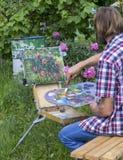 La pittura maschio dell'artista sull'aria del plein fiorisce le peonie rosa che dipingono sulla natura Fotografia Stock