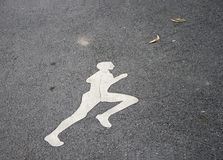 La pittura pareggiante bianca dell'uomo sul vicolo pareggiante funzionamento ad un passo delicato costante fotografia stock