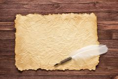 La piuma bianca e la vecchia carta su legno sorgono fotografie stock