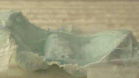 La piuma delicata bianca cade su un pannolino del bambino, sul concetto della comodità e sulla leggerezza per il bambino, il prim archivi video