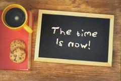 La pizarra con la frase el tiempo ahora se escribe en ella, al lado de la taza de café y de las galletas Imagen de archivo libre de regalías