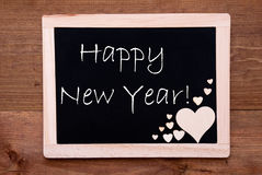 La pizarra con los corazones de madera, manda un SMS a Feliz Año Nuevo Imágenes de archivo libres de regalías
